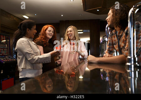 Three women making a toast with glasses of red wine at a bar. - Stock Photo