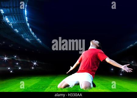 Soccer player celebrating goal on field of stadium - Stock Photo