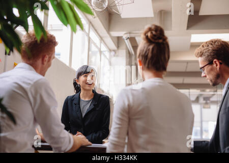 Diverse group of business people having meeting together in modern office. Businesswoman explaining new business - Stock Photo