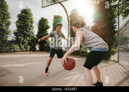 Young friends playing basketball together, boy in front of net blocking and other dribbling the ball on outdoor - Stock Photo