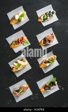 Italian crostini with various toppings on white baking paper - Stock Photo