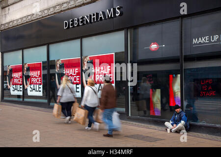 Out of focus blurred shoppers, people walking figures passing Half Price Autumn Sale signs at Debenhams Store, Manchester, - Stock Photo