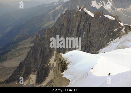 Climbers descend from Aiguille du Midi near Chamonix, France. - Stock Photo
