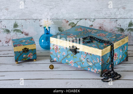 Hand made vintage style jewellery boxes on a rustic background - Stock Photo