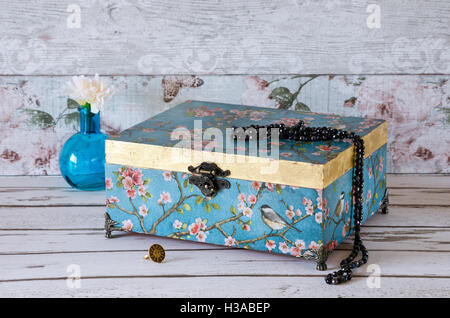 Stunning jewellery chest on a rustic background and decorated with a turquoise vintage paper and gold leaf - Stock Photo