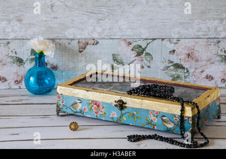 A stunning hand made jewelley box decoupaged and gilded on a rustic background - Stock Photo