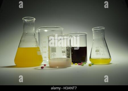 Science lab with colourful liquid chemicals in beakers, flasks and jugs. - Stock Photo