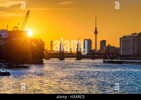 Classic view of Berlin skyline with famous TV tower and Oberbaum Bridge at river Spree in evening light at sunset, - Stock Photo