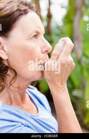 Woman using asthma inhaler - Stock Photo