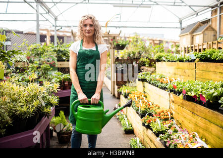 Female florist holding watering can - Stock Photo