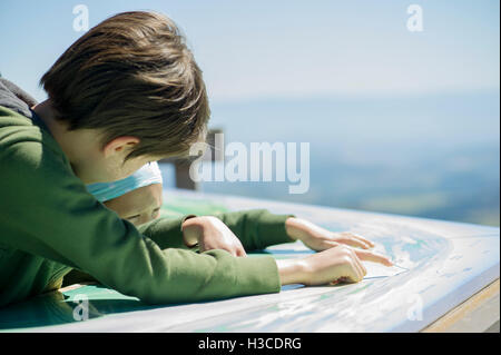 Young siblings studing map at scenic overlook - Stock Photo