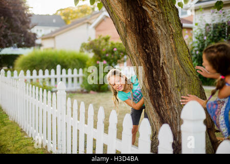 Happy sisters playing hide and seek in backyard - Stock Photo