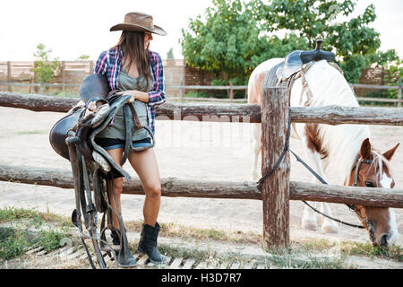 Happy beautiful young woman cowgirl in hat standing and holding saddle for riding horse - Stock Photo