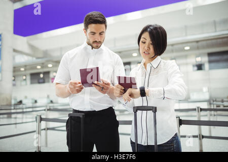 Business man and woman checking their passport - Stock Photo