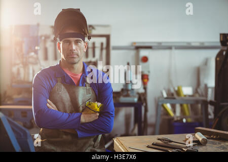 Portrait of male welder standing with arms crossed - Stock Photo