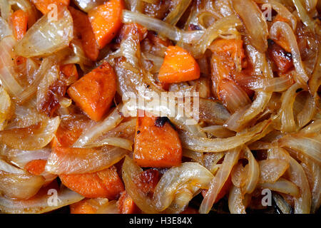 a fried onions and carrots in the pan, a bright background - Stock Photo