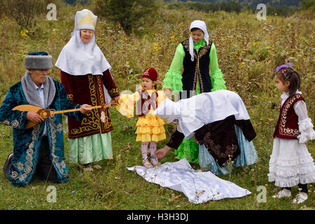 Tusau Kesu cutting the rope binding child's feet with scissors Kazakh traditional family ceremony with young girl - Stock Photo