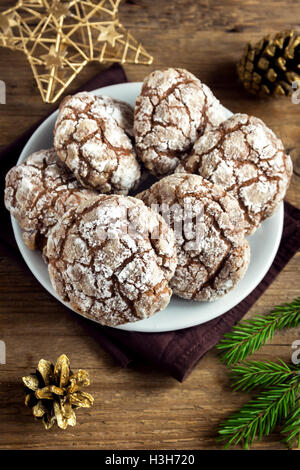 Chocolate crinkle cookies for Christmas with golden ornaments - homemade festive Christmas bakery - Stock Photo