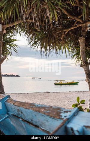 View of sea and boats between trees, Gili Meno, Lombok, Indonesia - Stock Photo