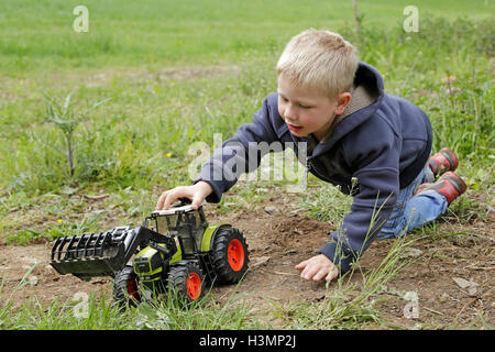 little boy playing with toy tractor - Stock Photo