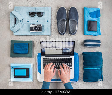 Overhead view of man's hands typing on laptop surrounded by travel packing items, with blue shirt,  retro camera, - Stock Photo