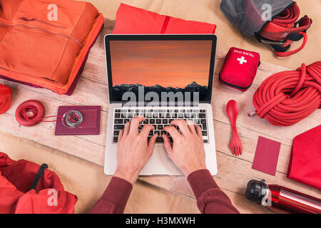 Overhead view of man's hands typing on laptop whilst preparing climbing equipment for travel - Stock Photo