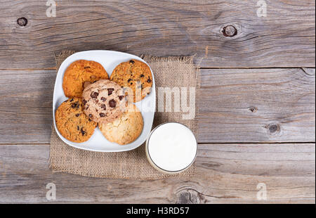 Overhead view of a variety of freshly baked cookies on a napkin with a glass milk. - Stock Photo