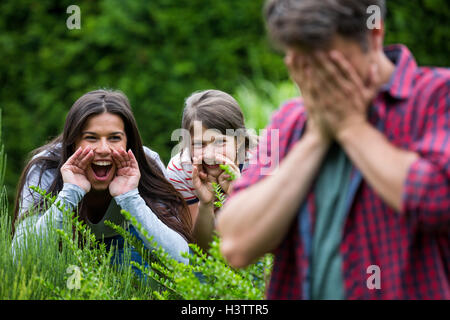Parents and daughter playing in park - Stock Photo