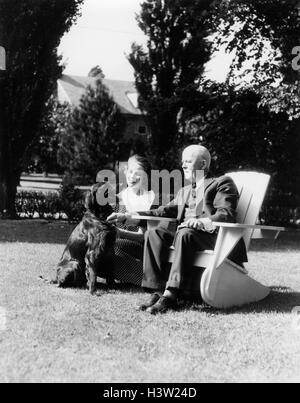 1930s ELDERLY MAN SITTING ON ADIRONDACK CHAIR IN YARD YOUNG WOMAN KNEELING NEXT TO HIM WITH IRISH SETTER DOG - Stock Photo