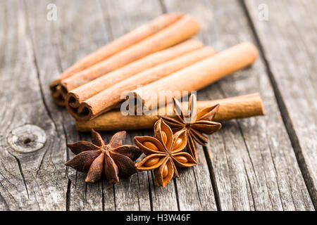 Cinnamon sticks and anise stars on old wooden table. - Stock Photo