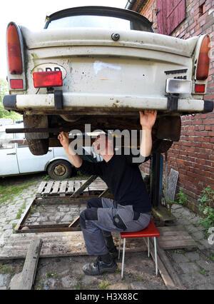 Der Trabant-Sammler Hanjo Aleit steht auf Trabant collector Hanjo Aleit works on a GDR Trabant from the 1980s on - Stock Photo