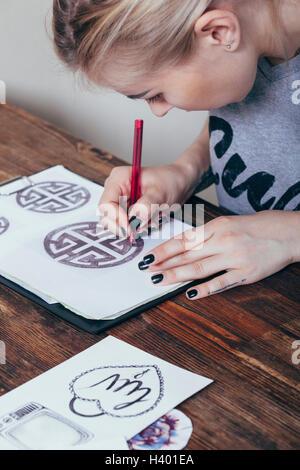 Close-up of tattoo artist drawing designs at art studio - Stock Photo