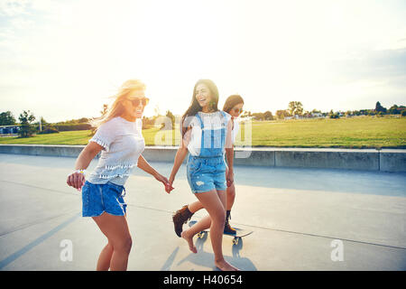 Three young female friends skateboarding at sunrise along a seaside promenade overlooking a green field as they - Stock Photo