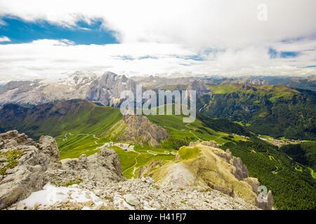 Pordoi pass mountain road and Marmolada mountain range seen from the Sass Pordoi plateau in Dolomites, Italy, Europe - Stock Photo