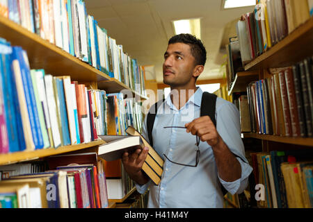 Young arab student reading book between the shelves in the library - Stock Photo
