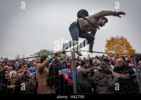 Refugee jumping across the fence to get out of the line for crossing the Slovenian-Austrian border in Spielfeld. - Stock Photo