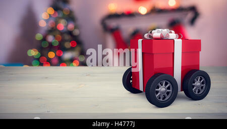 Composite image of gift box wrapped in red paper with ribbon on wheels - Stock Photo