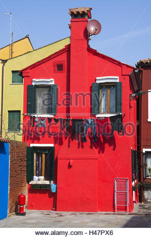Laundry hanging out to dry at a red painted house in the alleys on the island Burano, - Stock Photo