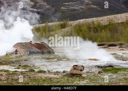 steam rising from geothermal hotspots and small smidur geysers at Geysir site Iceland - Stock Photo
