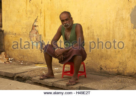 Asia, South-East Asia, Myanmar, Burma, Rangoon, Yangon, city centre, old man in the Longyi sits on red chair before - Stock Photo