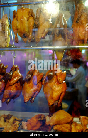 Cantonese style roasted ducks,chickens and pork hanging inside the window of a Chinese restaurant in Chinatown.Manhattan.New - Stock Photo