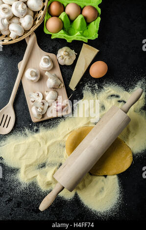 Making pasta from italian flour semolina, bio eggs, garlic, mushrooms tortellini at the end - Stock Photo