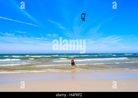 Kitesurfer sailing on blue sea with waves in Bialogora coastal village, Baltic Sea, Poland - Stock Photo