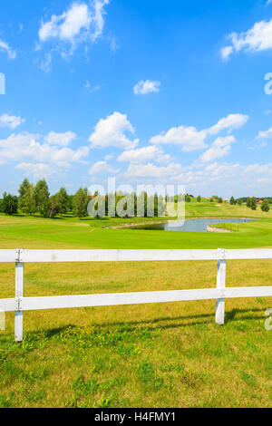 White wooden fence of golf course green area in Paczultowice village near Krakow on sunny summer day, Poland - Stock Photo