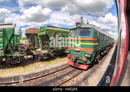 Freight train standing at a railway station in summer day. Cargo train logistic - Stock Photo