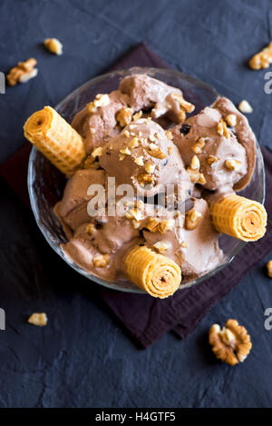 Homemade chocolate ice cream with chocolate chips and chopped walnuts in bowl close up, rustic style - Stock Photo