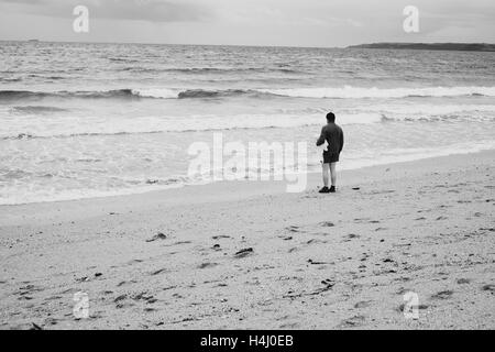 Man in a hat stands next to the sea with a towel under his arm as waves come in at Falmouths Gyllyngvase Beach 15 - Stock Photo