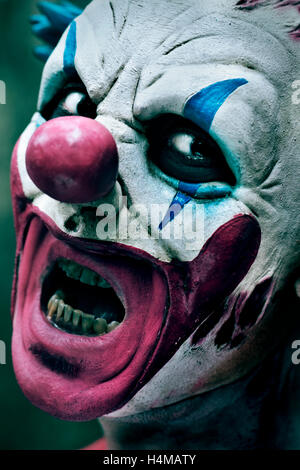 closeup of a scary evil clown with his mouth open showing his rotten teeth staring at the observer - Stock Photo