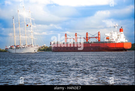 Freight Ship, entering the Port of Hamburg in the Light of the setting sun - Stock Photo