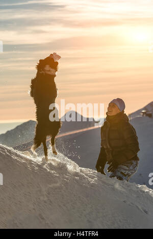 Border collie dog playing in the snow with his mistress in te mountain - Stock Photo